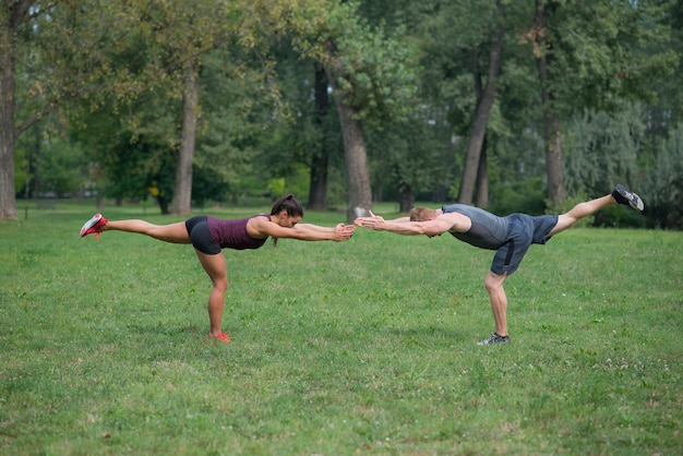 Training der jungen frau mit ihrem persönlichen trainer im park Premium Fotos