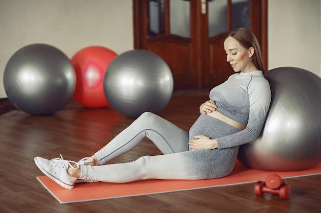 Training der schwangeren frau in einer turnhalle Kostenlose Fotos