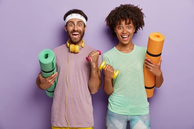 Trainings-, fitness- und sportkonzept. fröhliche gemischte paare trainieren, heben mit hanteln die arme, halten matten, trainieren im fitnessstudio. sportliche familien treiben gemeinsam sport. gesunder lebensstil Kostenlose Fotos