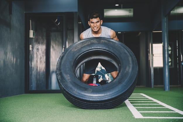 Trainingskonzept; übendes training des jungen mannes in der klasse; gefühl von engagement und geduld beim gewichtheben mit großen reifen Premium Fotos