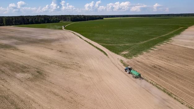 Traktor angetriebenes organisches düngemittel auf dem feld Premium Fotos