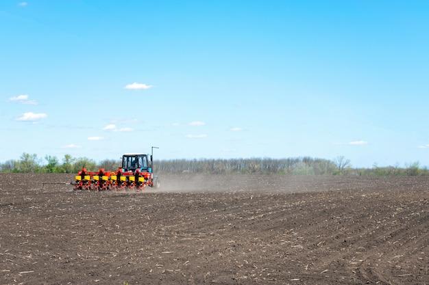 Traktor sät mais auf einem gepflügten feld Premium Fotos