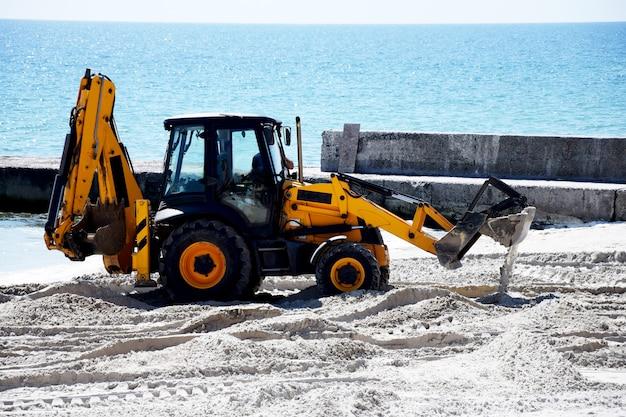 Traktor und sand. reparaturarbeiten am strand. Premium Fotos