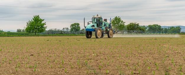 Traktor zum versprühen von unkraut und schädlingen auf dem feld Premium Fotos