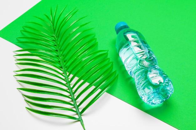 Transparente flüssige flasche mit tropischen palmblättern, draufsicht Premium Fotos