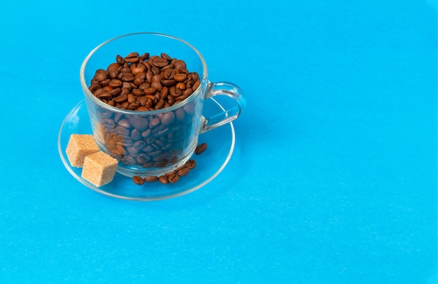Transparente glasschale mit kaffeebohnen mit scheiben des rohzuckers auf blau Premium Fotos