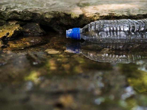 Transparente leere plastikwasserflasche, die auf wasser schwimmt Kostenlose Fotos