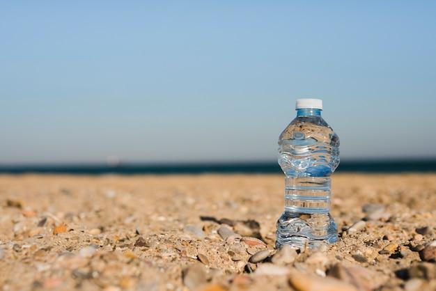 Transparente plastikwasserflasche im sand am strand Kostenlose Fotos