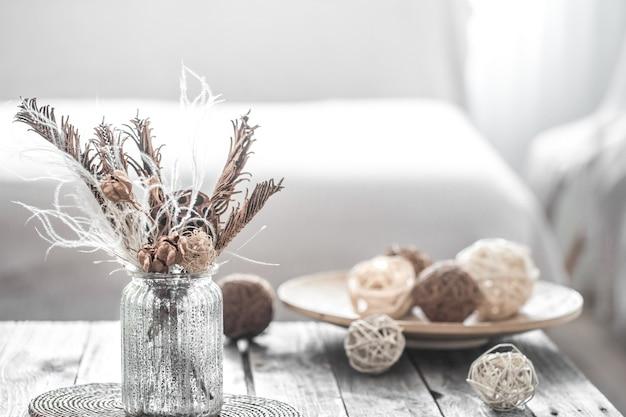 Transparente vase mit getrockneten blumen und teller mit fäden Kostenlose Fotos