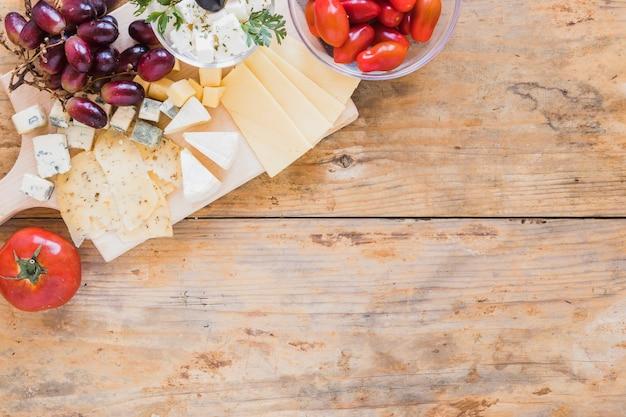 Trauben, kirschtomaten und käse auf hölzernem schreibtisch Kostenlose Fotos