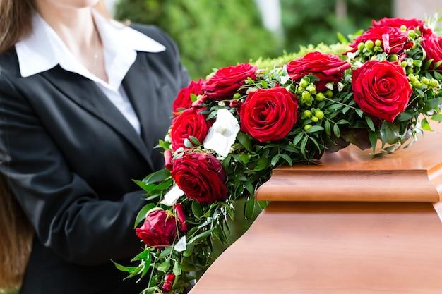 Trauernde frau bei der beerdigung mit sarg Premium Fotos