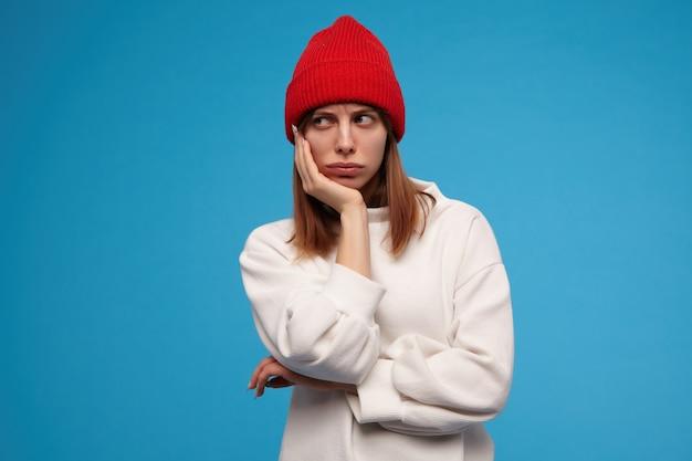Traurig aussehende frau, schönes mädchen mit brünetten haaren. tragen eines weißen pullovers und eines roten hutes. legen sie ihren kopf auf eine hand. fühlt sich gelangweilt. beobachten sie links den kopierbereich, isoliert über der blauen wand Kostenlose Fotos