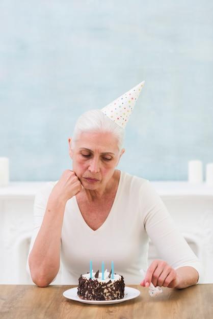 Traurige ältere frau, die geburtstagskuchen mit kerze über tabelle betrachtet Kostenlose Fotos