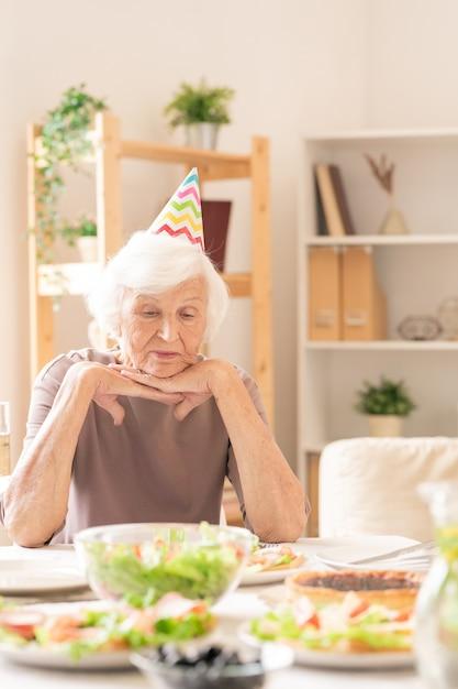 Traurige ältere frau in geburtstagskappe, die hausgemachtes essen beim sitzen am servierten tisch betrachtet Premium Fotos