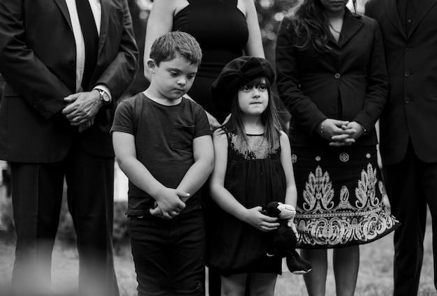 Traurige enkelkinder stehen am grab Premium Fotos