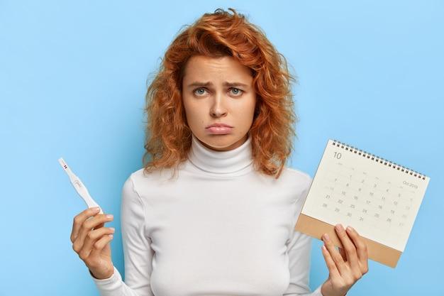 Traurige enttäuschte rothaarige frau hält schwangerschaftstest und menstruationskalender Kostenlose Fotos
