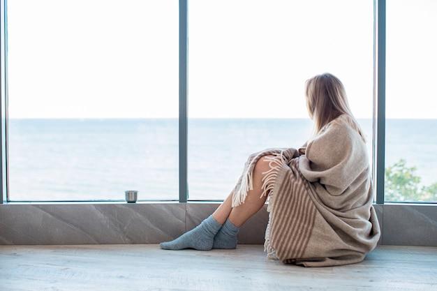 Traurige frau, die auf einem warmen boden in socken eingewickelt in einer woolen decke nahe dem großen fenster im licht sitzt. herbststimmung, wärme und gemütlichkeit. Premium Fotos
