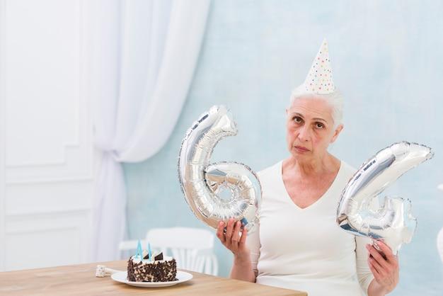 Traurige frau, die folienballon mit kuchen auf holztisch hält Kostenlose Fotos