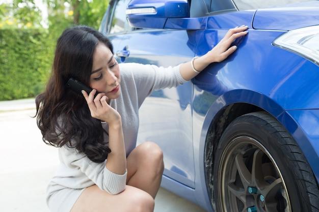 Traurige frau, die nahe autosorge um reifen sitzt und telefonisch mit kraftfahrzeugmechaniker spricht Premium Fotos
