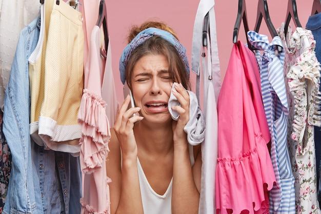 Traurige frau, die panik hat, während sie nichts zum anziehen hat, durch kleiderständer schaut, über smartphone spricht und vor unzufriedenheit weint. Kostenlose Fotos
