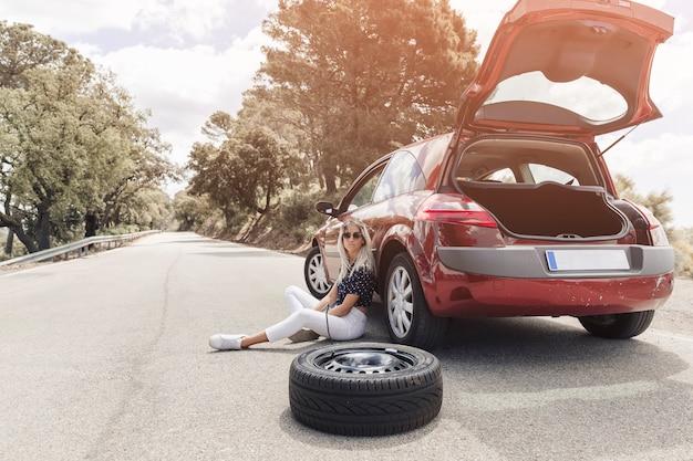 Traurige junge frau, die nahe dem aufgegliederten auto auf gerader straße sitzt Kostenlose Fotos