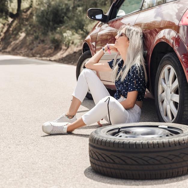 Traurige junge frau, die nahe dem aufgegliederten auto auf straße sitzt Kostenlose Fotos