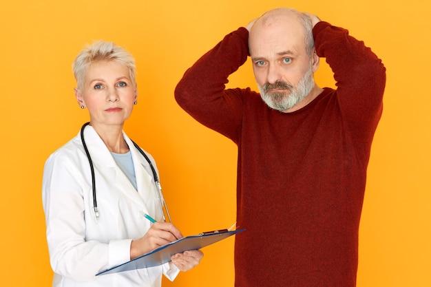 Traurige pensionierte weibliche praktizierende im weißen medizinischen mantel, der zwischenablage hält, erzählt ihrem älteren patienten über diagnose und behandlung Kostenlose Fotos