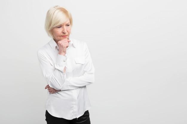 Traurige und alte frau denkt über etwas nach. sie hat einige gesundheitliche probleme, deshalb sieht sie überhaupt nicht sicher aus. schnittansicht. Premium Fotos