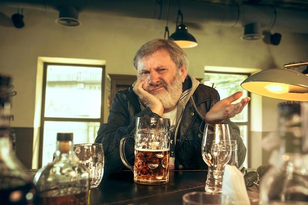 Trauriger älterer mann, der alkohol in der kneipe trinkt Kostenlose Fotos