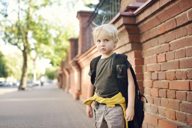Trauriger betonter kleiner junge mit rucksack. Premium Fotos