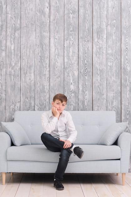 Trauriger junge, der zu hause auf dem sofa betrachtet kamera sitzt Kostenlose Fotos