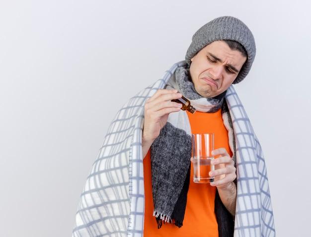 Trauriger junger kranker mann, der wintermütze mit schal trägt, der in plaid eingewickelt wird, das medikament in glas wasser gießt Kostenlose Fotos