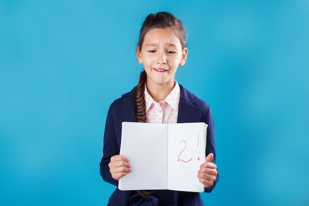 Trauriges betontes studentenmädchen, das schlechte ergebnisse der prüfung in ihrem notizbuch zeigt Premium Fotos