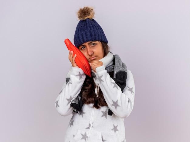 Trauriges junges krankes mädchen, das wintermütze mit schal trägt, der heißen wassersack auf wange lokalisiert auf weiß setzt Kostenlose Fotos