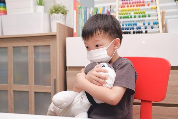 Trauriges kleines asiatisches kindergartenkind, das sein plüschtier des hundes sowohl in medizinischen schutzmasken als auch in gesichtsmasken umarmt Premium Fotos