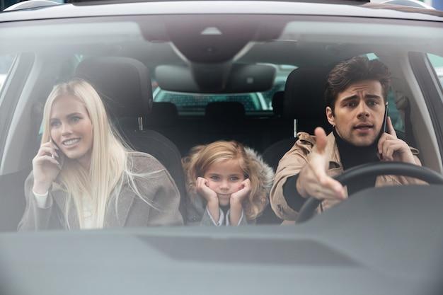 Trauriges kleines mädchen, das im auto sitzt, während ihre eltern sprechen Kostenlose Fotos
