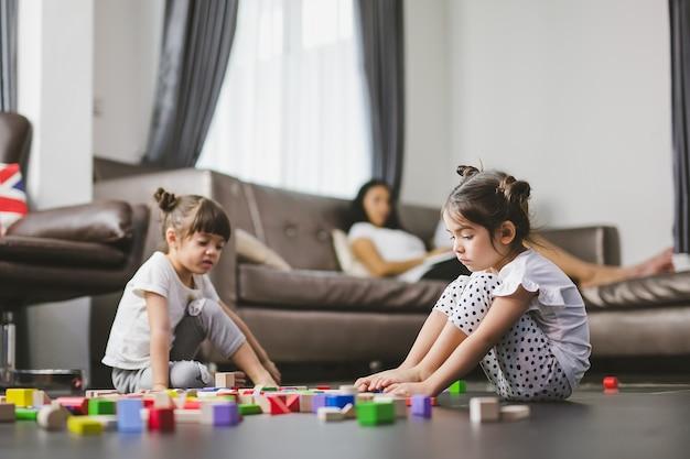 Trauriges mädchen der familie, das auf dem fußboden sitzt, ihre schwester, die die spielwaren spielt und mutter, die zusammen ihre töchter schaut. Premium Fotos