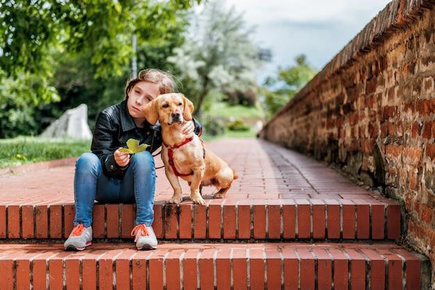 Trauriges mädchen mit dem hund, der auf der treppe sitzt Premium Fotos