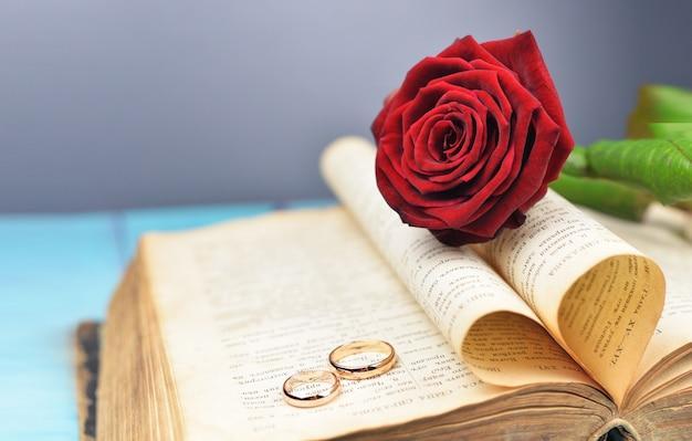Trauringe auf einer hochzeit mit einer roten rose auf einem alten buch Premium Fotos