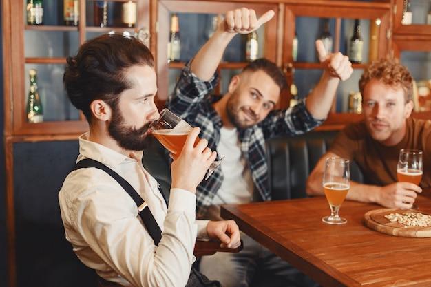 Treffen mit den besten freunden. drei glückliche junge männer in freizeitkleidung sprechen und trinken bier, während sie zusammen in der bar sitzen. Kostenlose Fotos