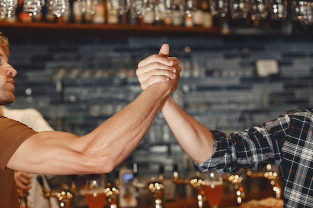 Treffen mit den besten freunden. zwei glückliche junge männer in freizeitkleidung sprechen und trinken bier, während sie zusammen in der bar sitzen. Kostenlose Fotos