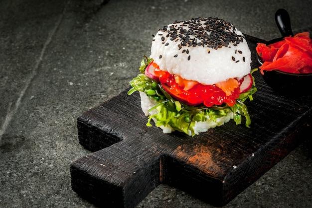 Trend hybrid food. japanische asiatische küche. sushi-burger, sandwich mit lachs, hayashi wakame, daikon, ingwer, roter kaviar. schwarzer steintisch mit sojasauce. kopieren sie platz Premium Fotos