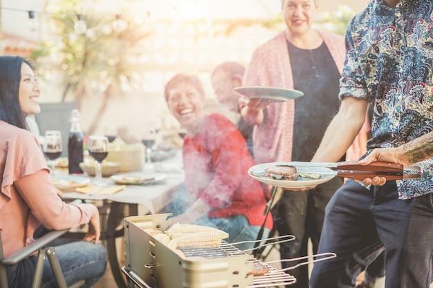 Trendiger mann, der fleisch am grillabendessen im freien kocht und dient Premium Fotos