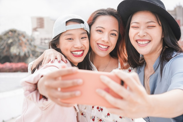 Trendy asiatische mädchen machen video-story für soziale netzwerk-app im freien. junge freundinnen, die spaß haben, selfie zu nehmen Premium Fotos