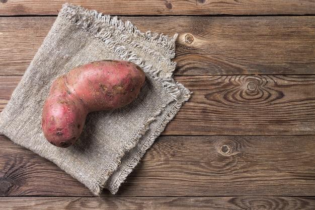 Trendy hässliche natürliche bio-kartoffel auf serviette, auf natürlichem holztisch. speicherplatz kopieren. Premium Fotos