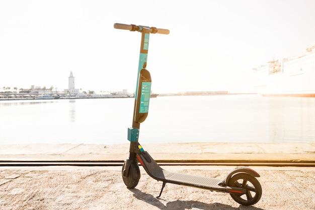 Tretroller geparkt in der nähe des docks Kostenlose Fotos