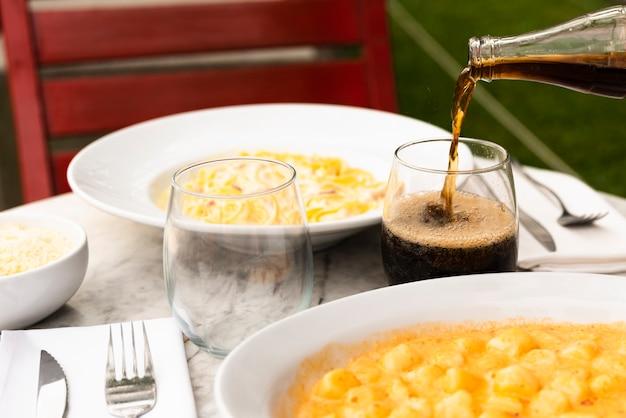 Trinken sie das gießen in das glas mit geschmackvollem italienischem teigwarenlebensmittel auf tabelle am restaurant Kostenlose Fotos