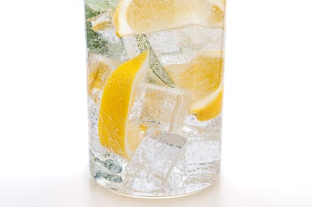 Trinken sie eis, die läppchen von frischer saftiger gelber zitrone und kristallwasser in einem glas. Premium Fotos