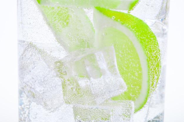 Trinken sie eis, frische, saftig grüne limetten und glasklares wasser in einem glas. Premium Fotos