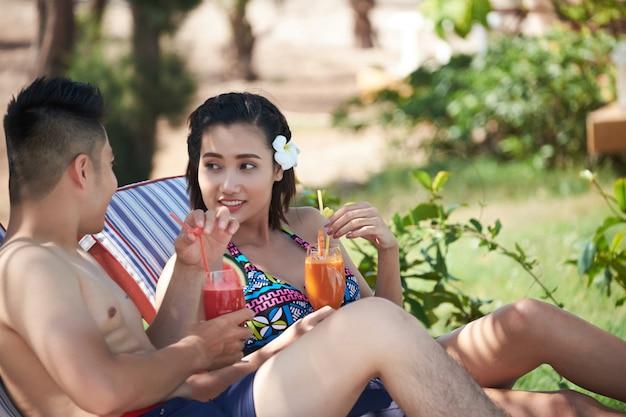 Trinkende cocktails des asiatischen mannes und der frau am luxuriösen tropischen erholungsort Kostenlose Fotos